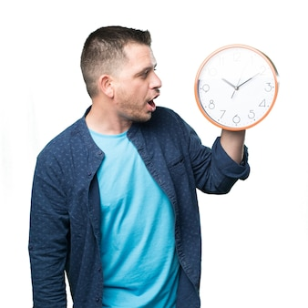 Young man wearing a blue outfit. Holding a clock. Looking surpri
