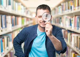 Young man wearing a blue outfit. Using a magnifying glass. Smili