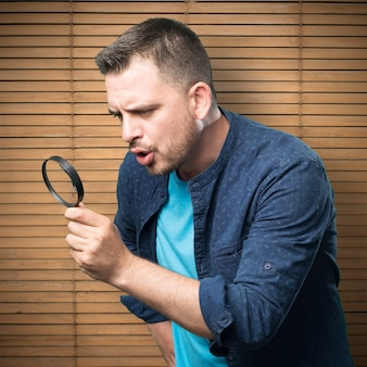Young man wearing a blue outfit. Using a magnifying glass.