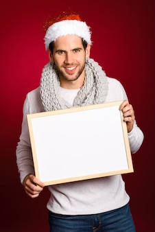Young man with a santa hat holding a blank board