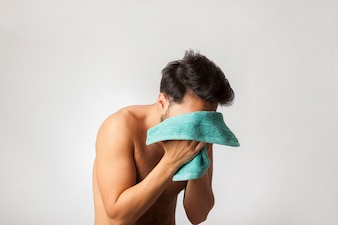 Young man with a towel on his face