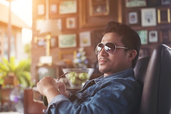 Young man with smartphone smiling relaxing at cafe.