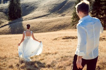 Young married couple walking by a field