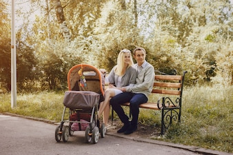 Young parents with stroller enjoying a day in the park