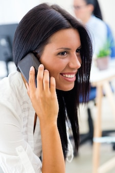 Young pretty business woman with mobile phone in her office.