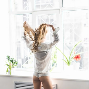 Young pretty woman standing at opened window and looking outside enjoys of rest