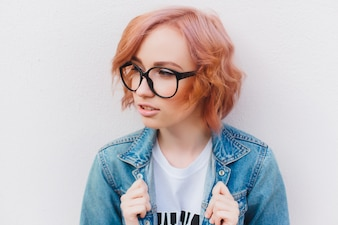 Young red-haired girl with glasses and a denim jacket