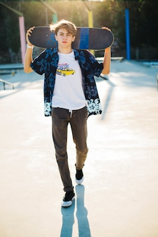 Young skater posing with his skateboard