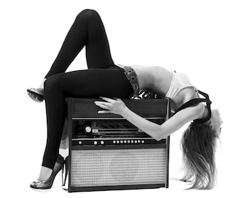Young slim woman wearing bra with old radio