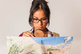 Young tourist woman with magnifying glass and map