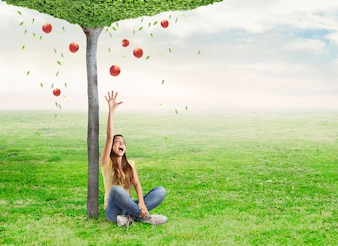Young woman being surprised by a red apple under a tree