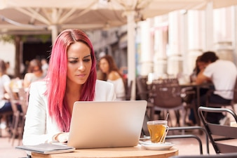 Young woman concentrated using a laptop at a table outside a cafe