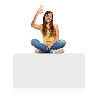 Young woman doing approval sign sitting on a banner