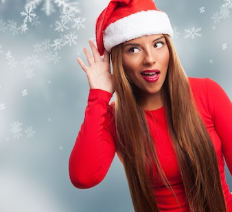 Young woman gesturing with her hand on christmas background