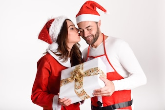 Young woman giving a christmas gift to his man with a kiss