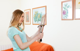 Young woman hanging pictures  at home