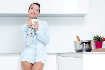 Young woman having a coffee at the kitchen