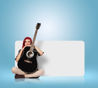 Young woman holding a classic guitar against a banner