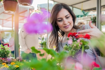 Young woman holding geranium in clay pot at garden center. Young woman shopping flowers at market garden centre