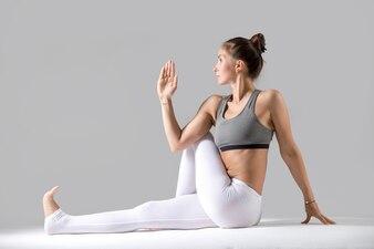 Young woman in Ardha Matsyendrasana pose, grey studio background