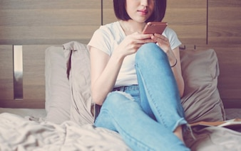 Young woman in casual clothes using smartphone and relaxing on bed, lifestyle concept