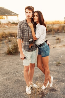 Young woman in shorts hugging her boyfriend