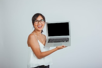 Young woman laughing and holding the laptop