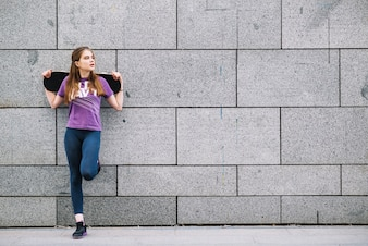 Young woman leaning against a grey tiled urban wall standing on one leg