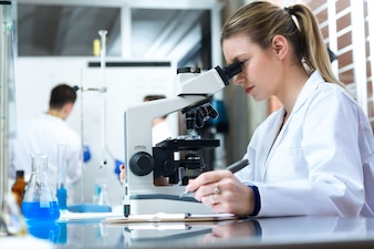 Young woman looking through microscope in laboratory.