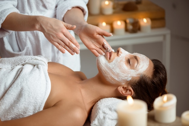 Young woman in mask for face relaxing in spa salon.
