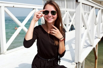 Young woman playing with her sunglasses and sitting on the pier