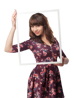 Young woman posing with a big frame