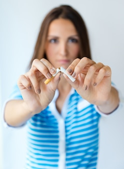 Young woman refuses to smoke and breaks cigarette.