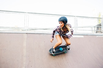 Young woman skating in the half pipe with helmet