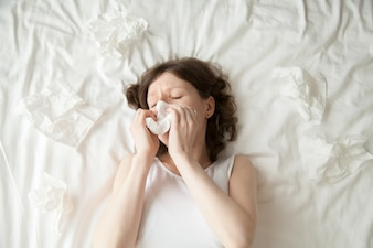 Young woman sneezing into tissue