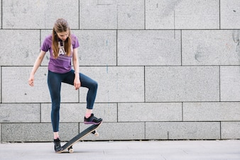 Young woman standing with skateboard