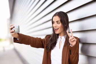 Young woman taking selfie photograph with smartphone doing V sig