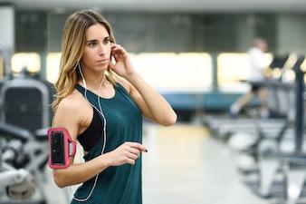 ジムでスマートフォンを立てている若い女性