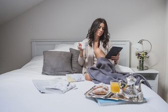 Young woman using tablet while having breakfast