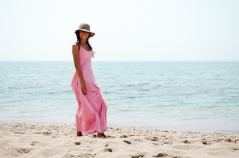 Young woman walking along the beach with pink dress