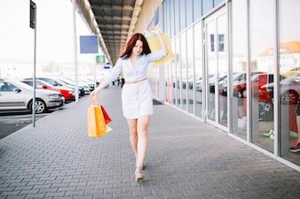 Young woman walking near shop-window