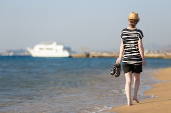 Young woman walking to white yacht