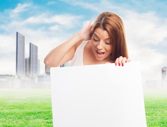 Young woman with blank board over cityscape