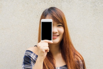 Young woman with brown hair smiling showing a blank smartphone screen standing on concrete wall background. Vintage effect style pictures.