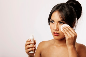 Young woman with cosmetic lotion and cotton pad