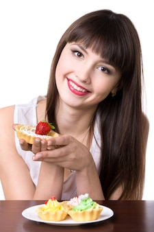 Молодая женщина с тарелкой тортов