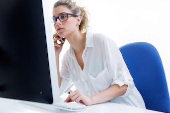 Young woman working from home on the computer and talking on the phone with the office