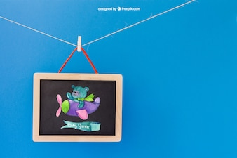 Baby mockup with slate hanging on clothes peg
