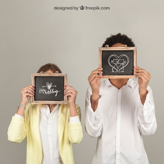 Couple holding slates in front of face