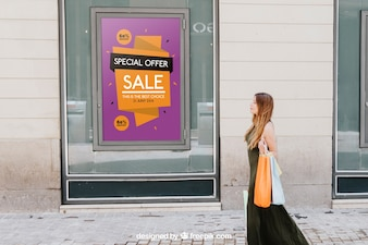 Design of mock up with sales poster and woman in the street